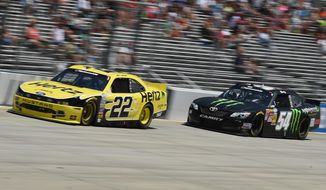Joey Logano (22) and Kyle Busch race during the NASCAR Nationwide series auto race, Saturday, May 31, 2014, at Dover International Speedway in Dover, Del. (AP Photo/Molly Riley)