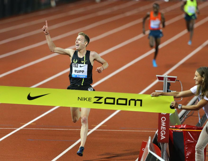 """Galen Rupp celebrates as he breaks his own American record in the 10,000 meters finishing in 26 minutes, 44.36 seconds during """"Distance Night in Eugene"""" at the Prefontaine Classic at Hayward Field in Eugene, Ore. on Friday, May 30, 2014. (AP Photo/The Register-Guard, Brian Davies)"""