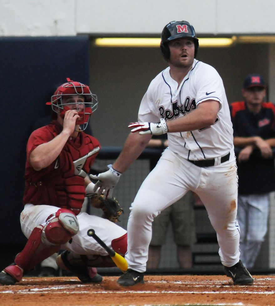 Mississippi's Sikes Orvis (24) hits an RBI double as Jacksonville State's Stephen Bartlett (33) watches at the NCAA Oxford Regional at Oxford-University Stadium on Saturday, May 31, 2014.  (AP Photo/The Oxford Eagle, Bruce Newman)