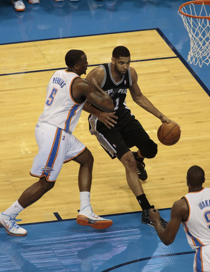 San Antonio Spurs forward Tim Duncan (21) drives on Oklahoma City Thunder center Kendrick Perkins (5) during the first half of Game 6 of the Western Conference finals NBA basketball playoff series in Oklahoma City, Saturday, May 31, 2014. (AP Photo Brett Deering)
