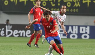 South Korea's Son Heungmin, left, fights for the ball against Tunisia's Bilel Mohsni during their friendly soccer match at World Cup stadium in Seoul, South Korea, Wednesday, May 28, 2014. South Korea will play against Belgium, Russia and Algeria in Group H of the World Cup 2014 in Brazil. (AP Photo/Ahn Young-joon)