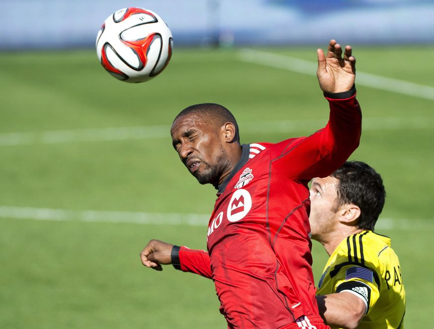 Toronto FC forward Jermain Defoe, left, heads the ball past Columbus Crew defender Michael Parkhurst during the first half of an MLS soccer game in Toronto on Saturday, May 31, 2014. (AP Photo/The Canadian Press, Nathan Denette)