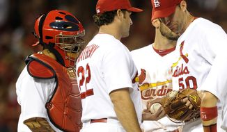 St. Louis Cardinals' starting pitcher Adam Wainwright (50) hands the ball to manager Mike Matheny (22) as he comes out of the game against the San Francisco Giants in the fifth inning as Cardinals' Yadier Molina, left, and Matt Carpenter, center back, look on during a baseball game on Friday, May 30, 2014, in St. Louis. (AP Photo/Bill Boyce)
