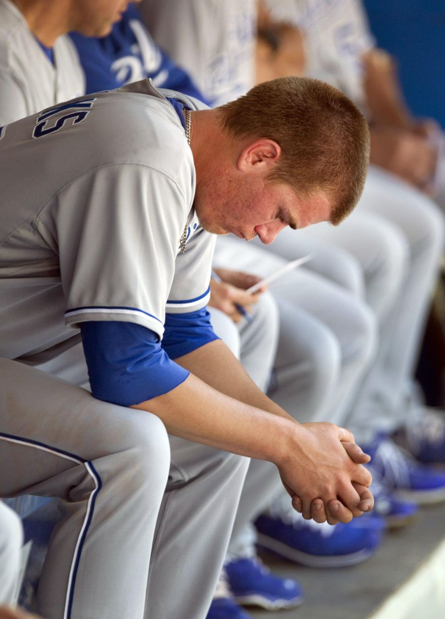 Kansas City Royals starting pitcher Aaron Brooks sits in the dugout after being taken out after he gave up seven runs to the Toronto Blue Jays in first inning of a baseball game in Toronto, Saturday, May 31, 2014. (AP Photo/The Canadian Press, Fred Thornhill)
