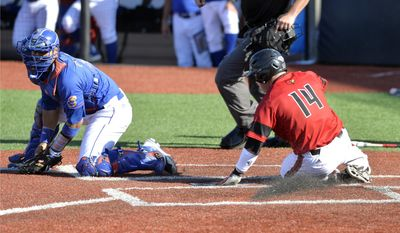 Louisville's Kyle Gibson, right, slides into home ahead of the relay throw to Kansas' Ka'iana Eldredge during an NCAA college baseball regional tournament game in Louisville, Ky., Saturday, May 31, 2014. (AP Photo/Timothy D. Easley)