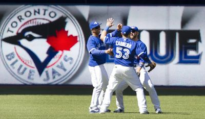 Toronto Blue Jays' Melky Cabrera, Anthony Gose and Kevin Pillar celebrate after their 12-2 win overhe Kansas City Royals 12-2 in a baseball game in Toronto, Saturday, May 31, 2014. (AP Photo/The Canadian Press, Fred Thornhill)