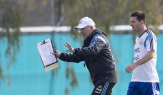 Argentina's coach Alejandro Sabella, left, gives instructions as player Lionel Messi walks behind during a team training session in Buenos Aires, Argentina, Wednesday, May 28, 2014. Argentina is training for the World Cup that starts in June in Brazil. (AP Photo/Natacha Pisarenko)