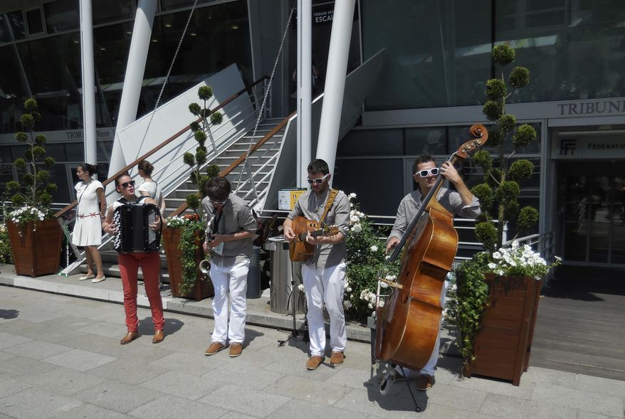 A four-piece band of roving musicians performs at Roland Garros stadium, belting out tunes while passers-by stop to take some snap shots, record a little video, or just listen to the soothing sounds of the ragtag mini concert, Saturday May 31, 2014 in Paris. The band consists of an accordion, a bass, a guitar and a bass clarinet. They can be found just about anywhere there are pedestrians. (AP Photo/Chris Lehouris)