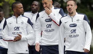 France's Patrice Evra, left,  Karim Benzema, center, and Franck Ribery arrive for a training session at the Clairefontaine training center, outside Paris, Thursday, May 29, 2014. France are preparing for the upcoming soccer World Cup in Brazil starting on 12 June. (AP Photo/Christophe Ena)