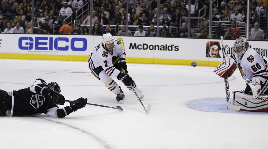 Chicago Blackhawks goalie Corey Crawford blocks a shot by Los Angeles Kings right wing Marian Gaborik, left, as defenseman Brent Seabrook wathes during second period of Game 6 of the Western Conference finals of the NHL hockey Stanley Cup playoffs in Los Angeles, Friday, May 30, 2014. (AP Photo/Chris Carlson)