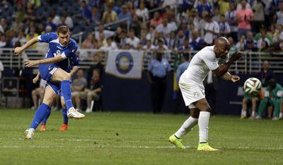 Bosnia-Herzegovina's Edin Dzeko, left, scores past Ivory Coast's Didier Zokora during the second half in an international friendly soccer match Friday, May 30, 2014, in St. Louis. Dzeko scored both goals in the team's 2-1 victory. (AP Photo/Jeff Roberson)
