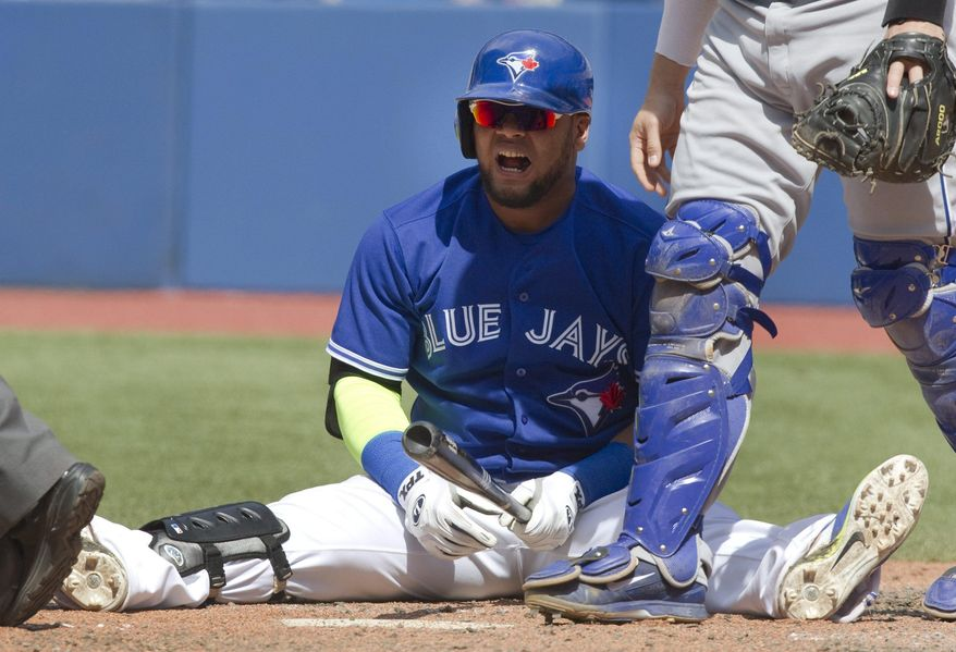 Toronto Blue Jays Juan Francisco sits on the ground after being hit by a pitch from Kansas City Royals Tim Collins during the seventh inning of a baseball game in Toronto, Saturday, May 31, 2014. (AP Photo/The Canadian Press, Fred Thornhill)