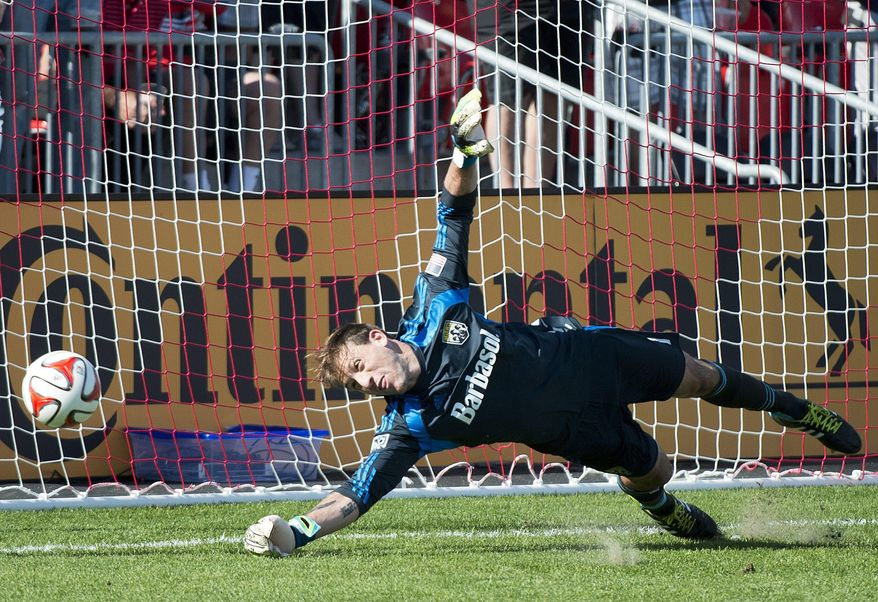 Columbus Crew goalkeeper Steve Clark is unable to make a save on a penalty kick by Toronto FC forward Jermain Defoe during the first half of a MLS soccer game in Toronto on Saturday May 31, 2014. (AP Photo/The Canadian Press, Nathan Denette)