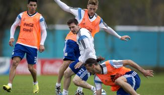 Argentina's national soccer players Martin Demichelis, right, Lionel Messi, center, and Lucas Biglia fight for the ball during a training session in Buenos Aires, Argentina, Saturday, May 31, 2014. Argentina is training for the Brazil 2014 World Cup.(AP Photo/Natacha Pisarenko)
