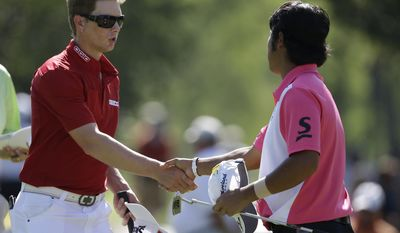 Chris Stroud, left, shakes hands with Hideki Matsuyama, of Japan, following the second round of the Memorial golf tournament on Friday, May 30, 2014, in Dublin, Ohio. (AP Photo/Darron Cummings)