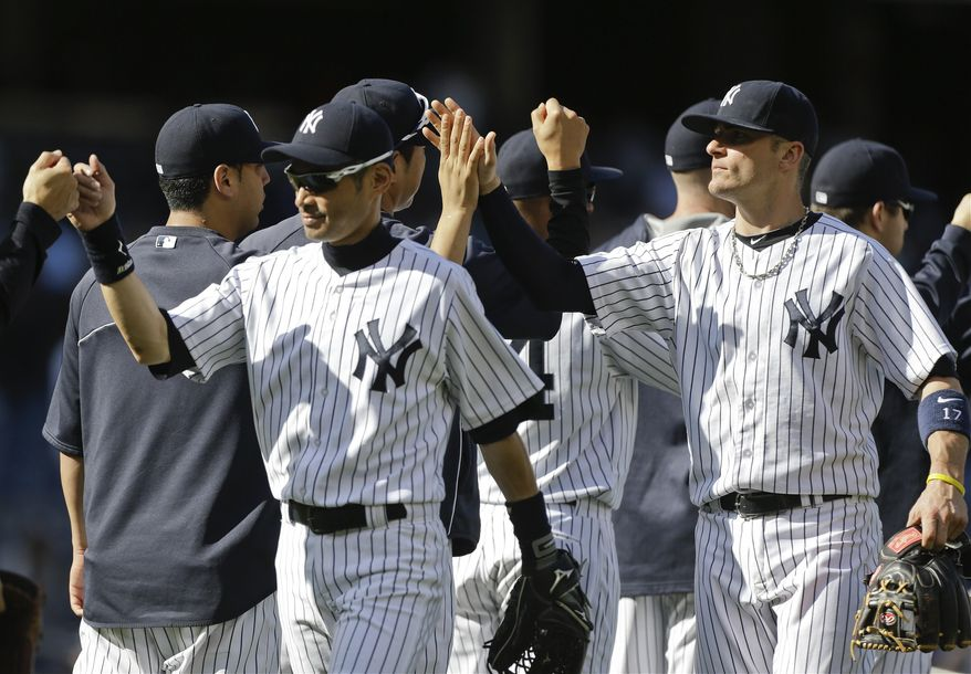 New York Yankees' Ichiro Suzuki, left, of Japan, and Brendan Ryan, right, celebrate with teammates after their 3-1 win in a baseball game against the Minnesota Twins Saturday, May 31, 2014, in New York. (AP Photo/Frank Franklin II)