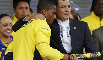 President Rafael Correa, right, hands the national flag to Antonio Valencia, captain of Ecuadorian nationasl soccer team during a farewell ceremony in Quito, Ecuador, Monday, May 26, 2014. While Ecuador went undefeated at home, beating every opponent in Quito except Argentina, with whom they drew, it failed to win on the road drawing just three times. Even so World Cup Fever has gripped the country with Ecuadorians excited about their squad's third appearance in the tournament. (AP Photo/Dolores Ochoa)
