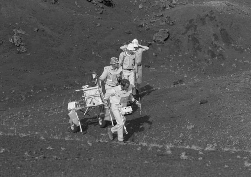 """This 1970 image provided by NASA shows Apollo 14 astronauts Alan Shepard, Edgar Mitchell and Stuart Roost and an unidentified man training with a Modularized Equipment Transporter on the Big Island of Hawaii. Before many Apollo astronauts went to the moon, they came to Hawaii to train on the Big Island's lunar landscapes. Now, decades-old photos are surfacing of astronauts scooping up Hawaii's soil and riding across volcanic fields in a """"moon buggy"""" vehicle. (AP Photo/NASA)"""