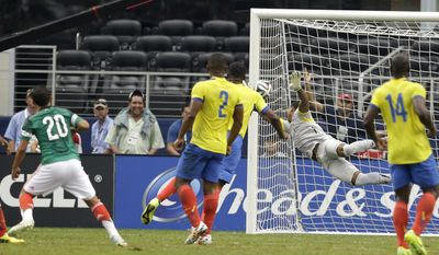 Mexico's Luis Montes (20) and Ecuador's Jorge Guagua (2) and Segundo Castillo (14) watch as a shot by Montes gets by Ecuador goalie Maximo Banguera for a score in the first half of a friendly soccer match, Saturday, May 31, 2014, in Arlington, Texas.  (AP Photo/Tony Gutierrez)