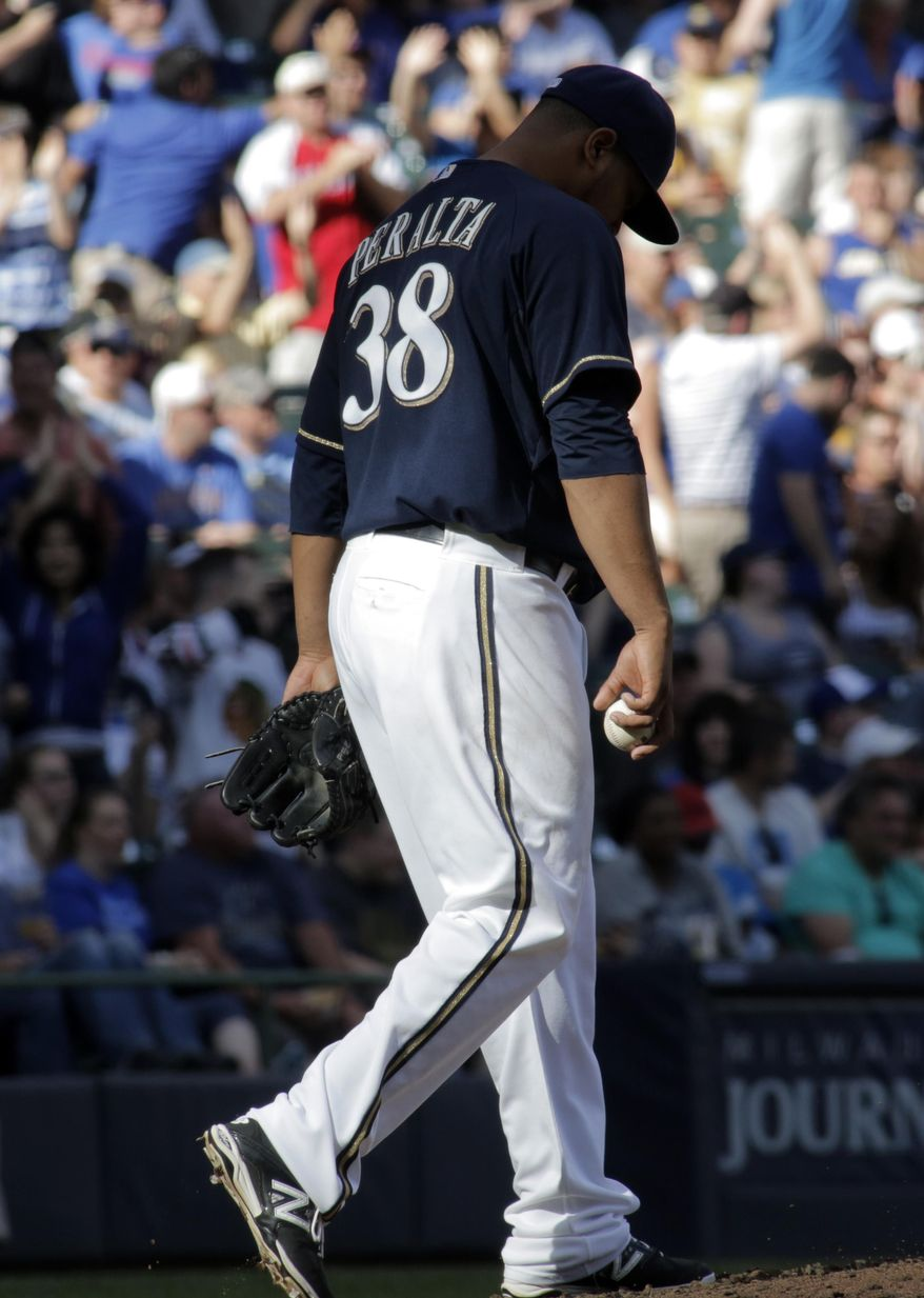 Milwaukee Brewers pitcher Wily Peralta reacts after giving up a two-run home run to Chicago Cubs' Anthony Rizzo, during the sixth inning of a baseball game Saturday, May 31, 2014, in Milwaukee. (AP Photo/Darren Hauck)