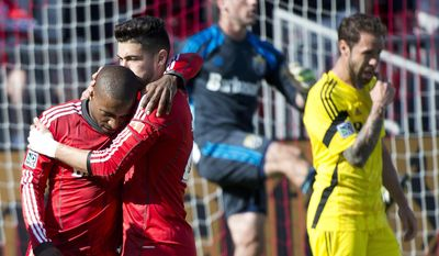 Toronto FC forward forward Jermain Defoe, left, celebrates his goal with teammate Jonathan Osorio, near Columbus Crew players during the first half of an MLS soccer game in Toronto on Saturday, May 31, 2014. (AP Photo/The Canadian Press, Nathan Denette)