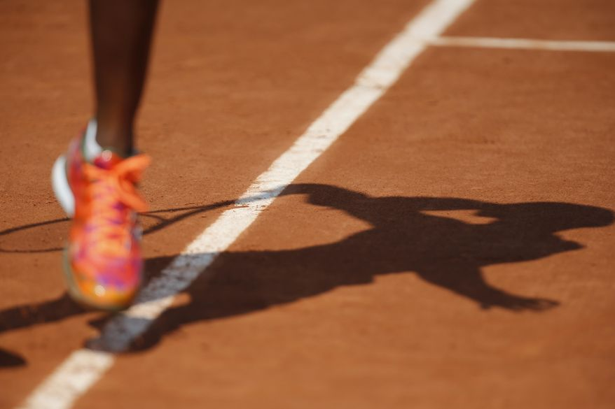 Sloane Stephens of the U.S. casts a shadow on the clay court as she serves the ball during the third round match of the French Open tennis tournament against Russia's Ekaterina Makarova at the Roland Garros stadium, in Paris, France, Saturday, May 31, 2014. Stephens won in two sets 6-3, 6-4. (AP Photo/David Vincent)