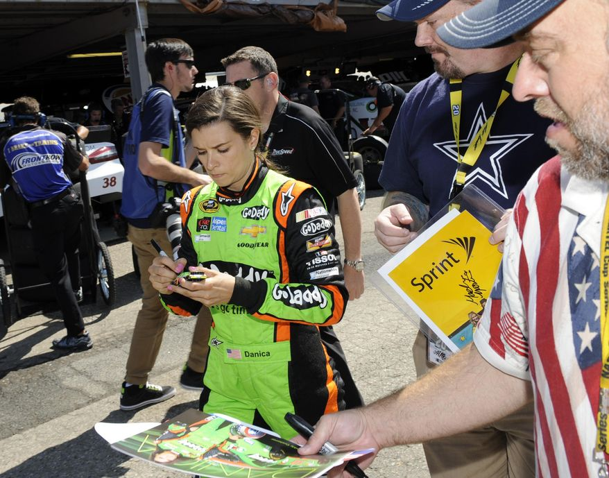 Danica Patrick signs for fans after practice for the NASCAR Sprint Cup series auto race, Saturday, May 31, 2014, at Dover International Speedway in Dover, Del. (AP Photo/Nick Wass)