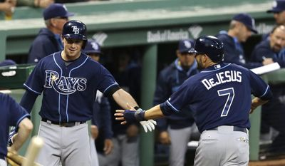 Tampa Bay Rays designated hitter David DeJesus (7) is congratulated by Evan Longoria after scoring against the Boston Red Sox on a ground-out by Ben Zobrist during the first inning of a baseball game at Fenway Park in Boston, Friday, May 30, 2014. (AP Photo/Charles Krupa)