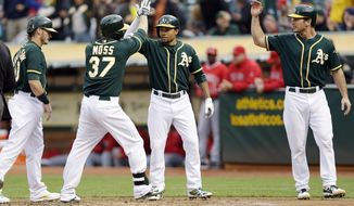 Oakland Athletics' Brandon Moss (37)  celebrates his a grand slam with teammates Josh Donaldson, left, Coco Crisp, center right, and John Jaso, against the Los Angeles Angels during the first inning of a baseball game Friday, May 30, 2014, in Oakland, Calif. (AP Photo/Marcio Jose Sanchez)