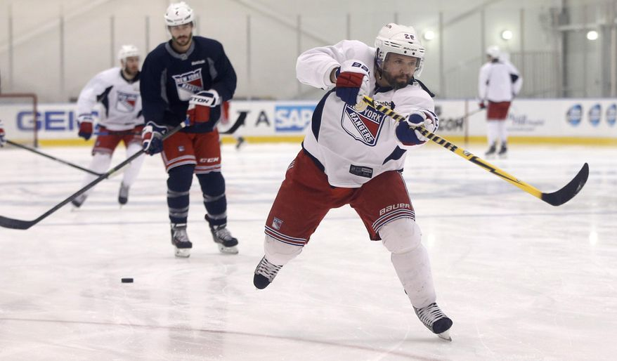 New York Rangers right wing Martin St. Louis, right, takes a shot on goal during a team practice at the Rangers training facility in Greenburgh, N.Y., Sunday, June 1, 2014.  (AP Photo/Kathy Willens)