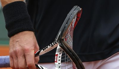 Latvia's Ernests Gulbis returns to his chair after breaking his racket as he plays Switzerland's Roger Federer during their fourth round match of  the French Open tennis tournament at the Roland Garros stadium, in Paris, France, Sunday, June 1, 2014. (AP Photo/Michel Euler)
