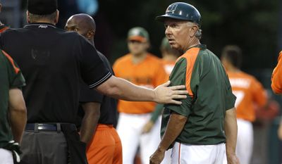 Miami head coach Jim Morris, right, is lead away by an umpire after the benches cleared between Miami and Texas Tech in the third inning during an NCAA college baseball regional tournament in Coral Gables, Fla., Sunday, June 1, 2014.  (AP Photo/Lynne Sladky)
