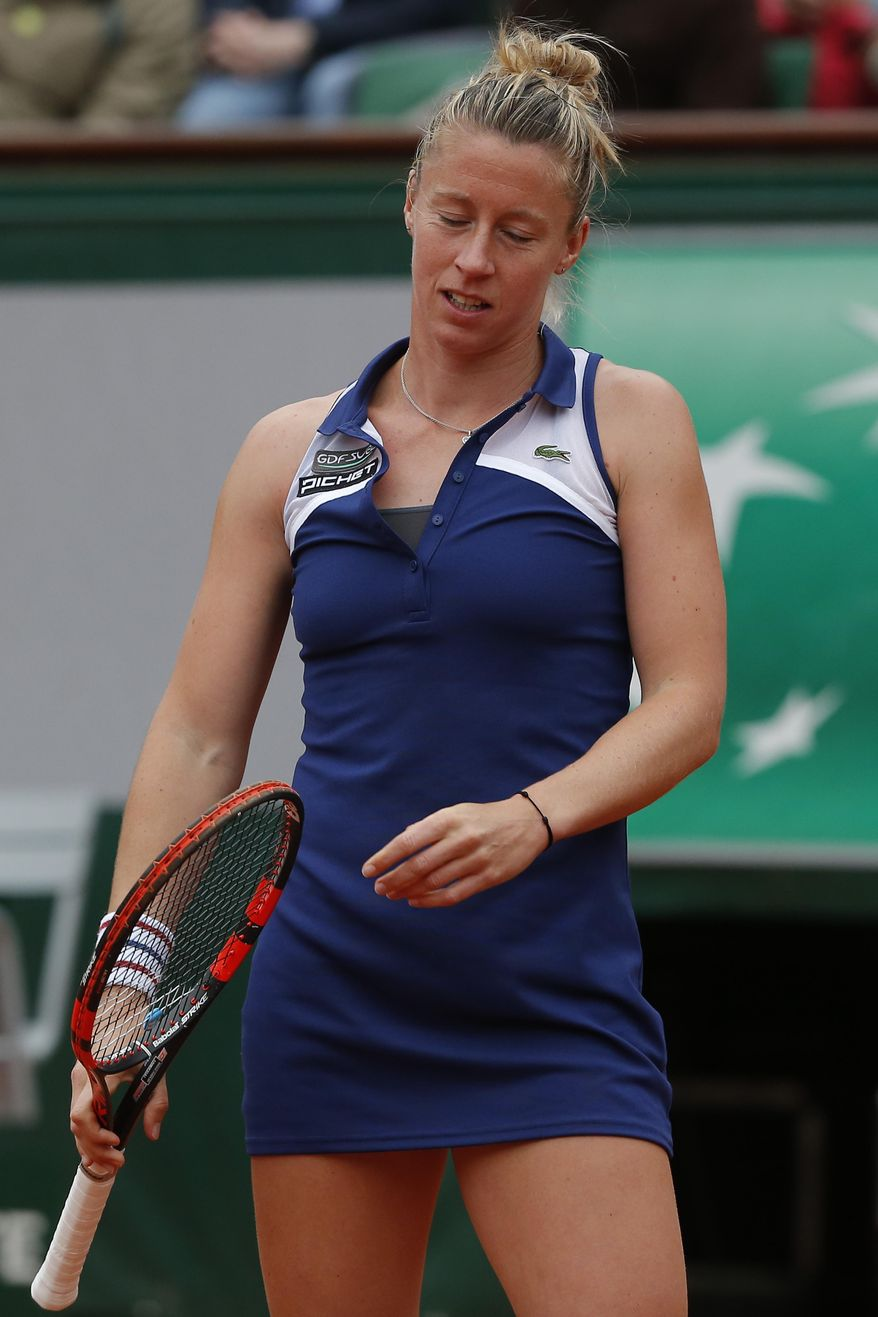 France's Pauline Parmentier misses a return during the fourth round match of the French Open tennis tournament against Spain's Garbine Muguruza at the Roland Garros stadium, in Paris, France, Sunday, June 1, 2014.  (AP Photo/Michel Euler)