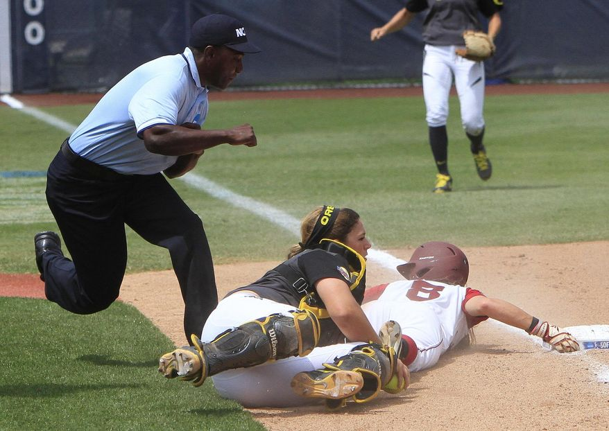 Oregon catcher Janelle Lindvall, center, runs down Alabama's Haylie McCleney (8) at third base for the out during the first inning of an NCAA Women's College World Series softball tournament game in Oklahoma City, Sunday, June 1, 2014. (AP Photo/Alonzo Adams)