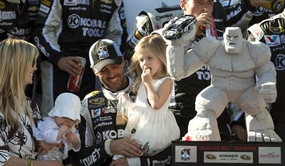 Jimmie Johnson celebrates winning the NASCAR Sprint Cup series auto race with his wife Chandra, left, and daughters Lydia and Genevieve, right, at Dover International Speedway, Sunday, June 1, 2014, in Dover, Del. (AP Photo/Molly Riley)