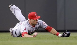 Los Angeles Angels center fielder Mike Trout dives for and barely misses a double by Seattle Mariners' James Jones in the fourth inning of a baseball game Thursday, May 29, 2014, in Seattle. (AP Photo/Elaine Thompson)