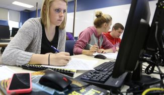 ADVANCE FOR USE SUNDAY, JUNE 1 - In this photo taken on Monday, May 12, 2013, sophomore Kristina Robey works on an assignment during a customer service strategies class at Dubuque Senior High School in Dubuque, Iowa. (AP Photo/The Telegraph Herald, Jessica Reilly)