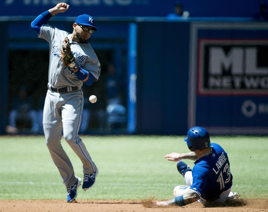 Kansas City Royals second baseman Omar Infante, left, forces out Toronto Blue Jays' Brett Lawrie, right, at second base but can't turn over the double play as he loses control of the ball during the fourth inning of a baseball game in Toronto on Sunday, June 1, 2014. (AP Photo/The Canadian Press, Nathan Denette)
