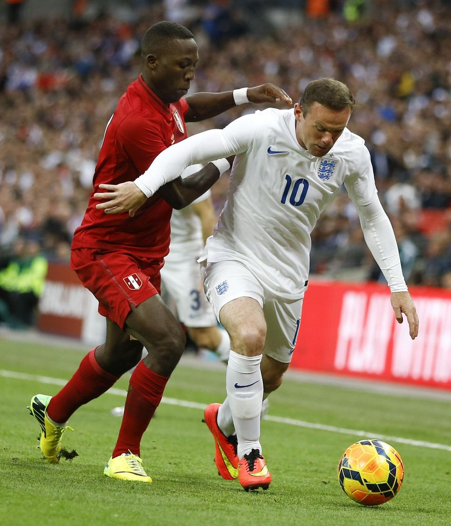 England's Wayne Rooney, right, competes for the ball with Peru's Luis Advincula during the international friendly soccer match between England and Peru at Wembley Stadium in London, Friday, May 30, 2014. (AP Photo/Kirsty Wigglesworth)