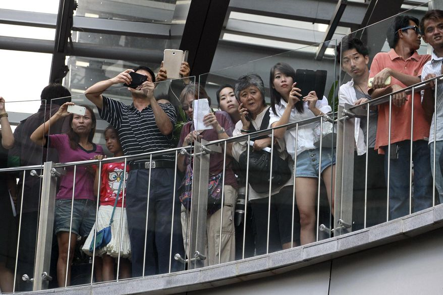 """Onlookers watch the cat-and-mouse game between Thai soldiers and anti-coup protesters at a shopping mall in Bangkok, Thailand Sunday, June 1, 2014. Hundreds of demonstrators shouting """"Freedom!"""" and """"Democracy!"""" gathered Sunday near the major shopping mall in downtown Bangkok to denounce the country's May 22 coup despite a lockdown by soldiers of some of the city's major intersections. (AP Photo/Wason Wanichakorn)"""