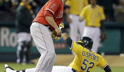 Oakland Athletics' Yoenis Cespedes (52) slides safely into third base past Los Angeles Angels' David Freese with a two run triple in the seventh inning of a baseball game Saturday, May 31, 2014, in Oakland, Calif. (AP Photo/Ben Margot)