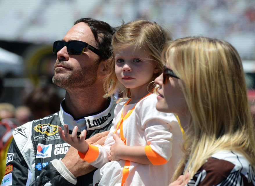 Jimmie Johnson, left, holds his daughter Genevieve with his wife Chandra, right, before driving in the NASCAR Sprint Cup series auto race at Dover International Speedway, Sunday, June 1, 2014, in Dover, Del. (AP Photo/Molly Riley)
