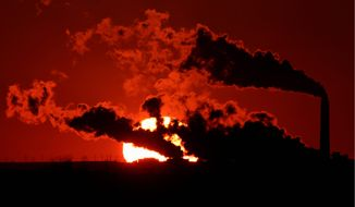Steam from the Jeffrey Energy Center coal-fired power plant near St. Marys, Kan., is silhouetted against the setting sun on March 8, 2014. (Associated Press) **FILE**