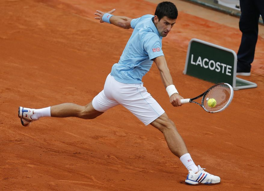 Serbia's Novak Djokovic returns the ball during the fourth round match of the French Open tennis tournament against France's Jo-Wilfried Tsonga at the Roland Garros stadium, in Paris, France, Sunday, June 1, 2014. (AP Photo/David Vincent)