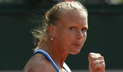 The logo of Roland Garros is seen as Netherlands' Kiki Bertens clenches her fist after scoring a point during the third round match of the French Open tennis tournament against Spain's Silvia Soler-Espinosa at the Roland Garros stadium, in Paris, France, Saturday, May 31, 2014. (AP Photo/Darko Vojinovic)