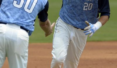 North Carolina's Skye Bolt (20) is congratulated by manager Mike Fox as he rounds third base after hitting a two-run home run during the first inning of an NCAA college baseball regional tournament game against Long Beach State in Gainesville, Fla., Sunday, June 1, 2014. (AP Photo/Phelan M. Ebenhack)