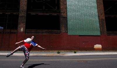 Jason Burke, 35, left, of Ridgewood, N.J., plays soccer near a warehouse adjacent to Red Bull Arena before the start of an international soccer friendly between Turkey and the United States, Sunday, June 1, 2014, in Harrison, N.J. (AP Photo/Julio Cortez)