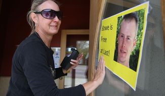 Sondra Van Ert, co-owner of Baldy Sports, hangs a sign celebrating news of U.S. Army Sgt. Bowe Bergdahl's release on Saturday, May 31, 2014 in Hailey, Idaho, his hometown. Bergdahl, 28, had been held prisoner by the Taliban since June 30, 2009. He was handed over to U.S. special forces by the Taliban in exchange for the release of five Afghan detainees held by the United States. (AP Photo/The Times-News, Ashley Smith)