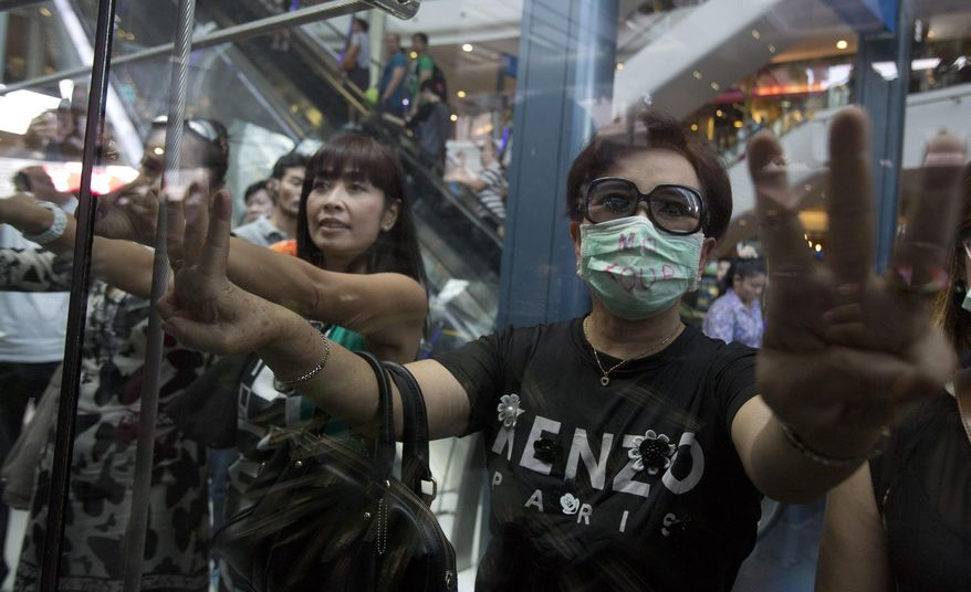 """Protesters show three fingers representing liberty, brotherhood and equality during an anti-coup demonstration in Bangkok, Thailand Sunday, June 1, 2014. Hundreds of demonstrators shouting """"Freedom!"""" and """"Democracy!"""" gathered Sunday inside major shopping mall in downtown Bangkok to denounce the country's May 22 coup despite a lockdown by soldiers of some of the city's major intersections.(AP Photo/Sakchai Lalit)"""