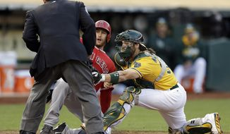 Los Angeles Angels' Chris Iannetta, center, is tagged out at home plate by Oakland Athletics catcher Derek Norris in the second inning of a baseball game Saturday, May 31, 2014, in Oakland, Calif. Iannetta was attempting to score on a single by Collin Cowgill. (AP Photo/Ben Margot)